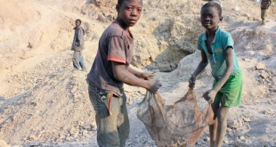 """Laden Tangeni and his friend sieving dirt from the small stones of raw copper they collected. SHARE assignment: s110732-1 Summary: Laden Tangeni, a 10-year-old boy, has been a worker in the copper mining quarry for two years now. He lives with his widowed mother, Chantal Kabwiza, in Kamatanda village, 100 metres from the quarry. He earns less than a dollar per-day after working long hours in bare feet. """"The money from Kamatanda allows me to buy bread and keep some for my family,"""" states Laden.  Location: Kamatanda village, Likasi, DR Congo"""