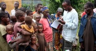 Carnet à mains, un préposé du HCR entrain d'enregistré une famille de pygmées dans un centre des déplacés de Dongo(RDC) à Betou(RCA) le 18/11/2009. Ph. Don John Bompengo